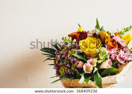 Bouquet of colorful flowers on white wall - stock photo