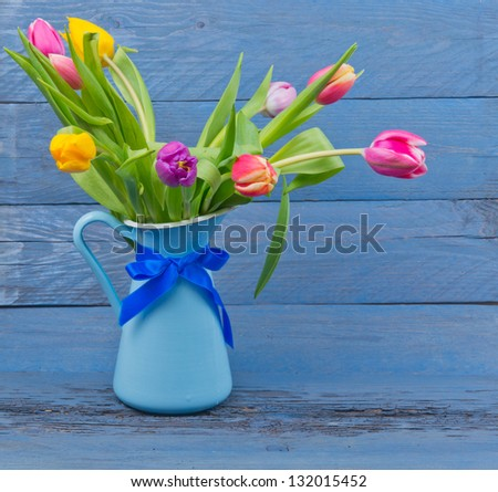 Bouquet of colorful tulips in a blue jug on blue wooden table