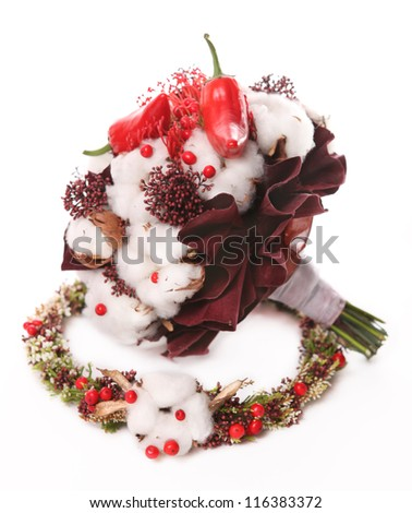 bouquet of cotton pods, red berries and red pepper on the background of a wreath