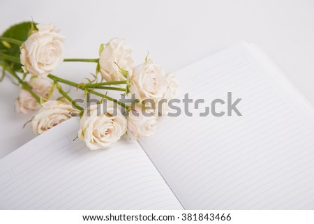 Bouquet of creamy roses lying on open notebook.