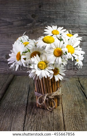 Bouquet of daisies in a bamboo vase on a wooden surface