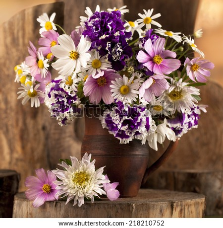 bouquet of daisies in ceramic jug - stock photo