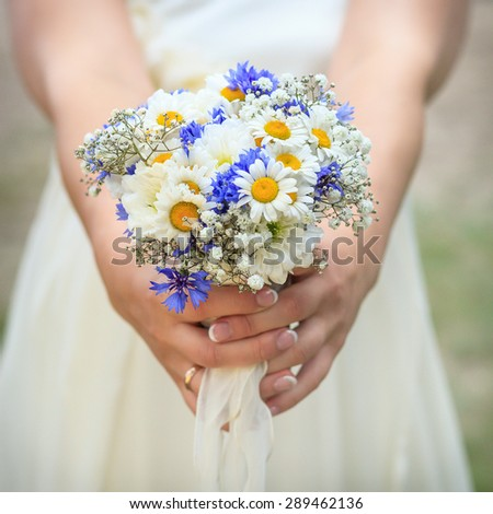 Bouquet of daisies in hands of bride. Shallow depth of field - stock photo