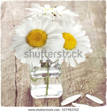 Bouquet of daisies on a vintage wooden surface - stock photo