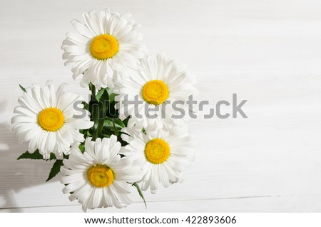 bouquet of daisies on white wooden table - stock photo