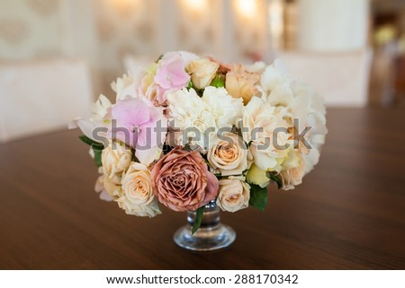 bouquet of flowers in a vase on a brown wood background  - stock photo