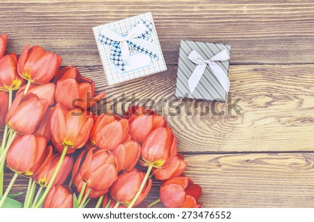 Bouquet of Fresh Orange Tulip Flowers on Top of Wooden Table with Two Gift Boxes, Captured in High Angle View. - stock photo