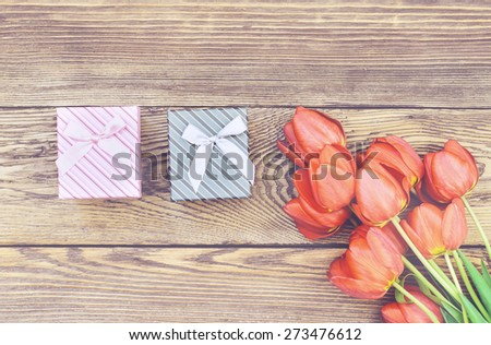 Bouquet of Fresh Orange Tulip Flowers on Top of Wooden Table with Two Gift Boxes, Captured in High Angle View.