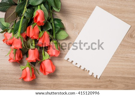 Bouquet of fresh pink red roses on wooden background. Floral romantic arrangement with blank card. - stock photo