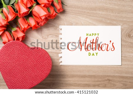 Bouquet of fresh pink red roses with gift on wooden background. Floral romantic arrangement with card text Happy Mother's Day. - stock photo