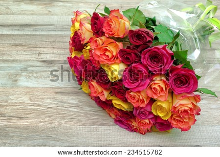 bouquet of fresh roses on a wooden background close-up. horizontal photo. - stock photo