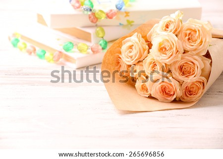 Bouquet of fresh roses wrapped in paper with books and beads on wooden background - stock photo