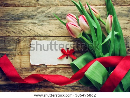 bouquet of fresh tulips on old wooden table, blank paper tag with red bow - stock photo