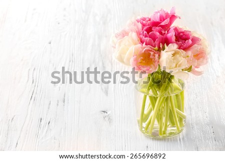 Bouquet of fresh tulips on wooden background - stock photo