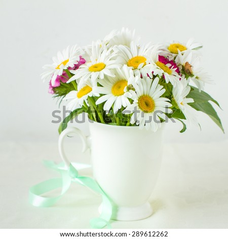 Bouquet of garden flowers in rustic white mug - stock photo