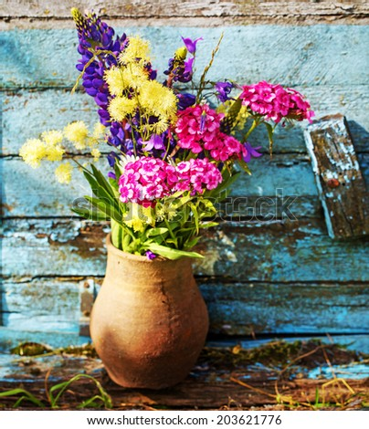 bouquet of garden flowers on old wooden bench  - stock photo