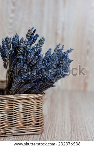 Bouquet of lavender in a wicker basket on a wooden background - stock photo