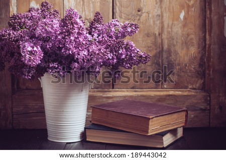 Bouquet of lilac flowers in a pot and old books on a background of vintage wooden board, home decor in a rustic style - stock photo