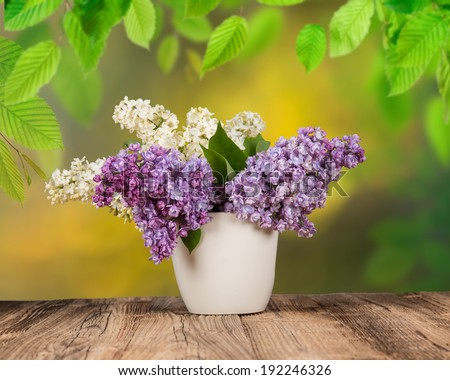 bouquet of lilac flowers in flower pot on wooden table. - stock photo