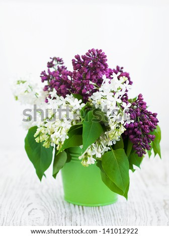 Bouquet of  lilac in a green bucket on a wooden background