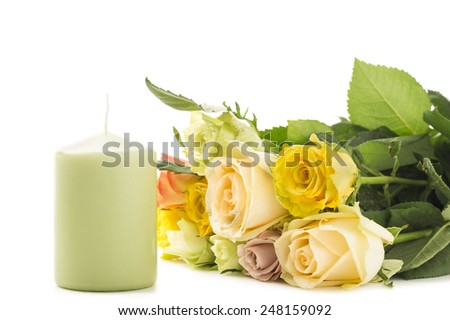 Bouquet of multicolored roses on white background beside a green candle symbolic of love and romance for an anniversary, Valentines Day or Mothers Day or as a tribute of remembrance to a loved one - stock photo