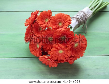 Bouquet of orange gerbera daisies, green plank background, holiday concept - stock photo