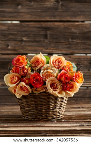 Bouquet of orange roses in basket on brown wooden background - stock photo