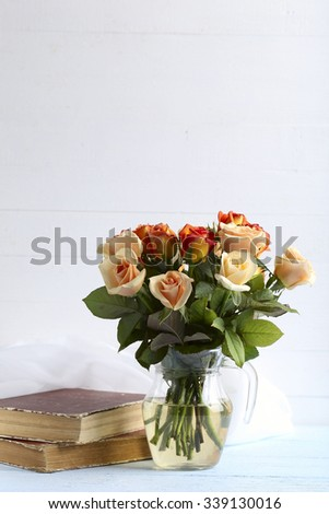 Bouquet of orange roses in vase on blue wooden background - stock photo