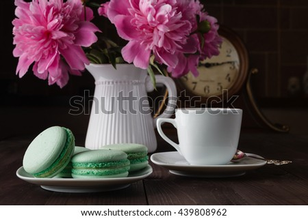 Bouquet of peonies blooms in vase with macaroons - stock photo