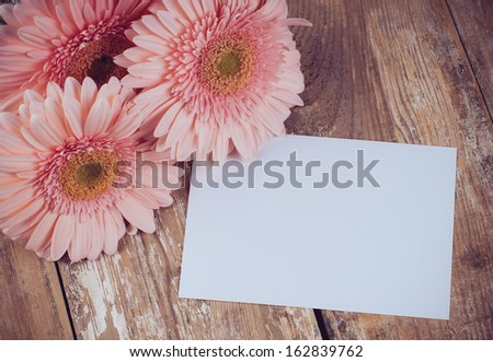 Bouquet of pink gerberas and a blank white cardboard on a wooden board, vintage style, close-up - stock photo