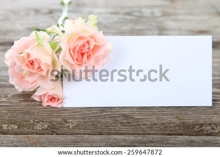 Bouquet of pink roses and greeting card on a wooden background - stock photo