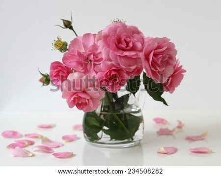 Bouquet of pink roses in a glass vase. Floral still life. - stock photo