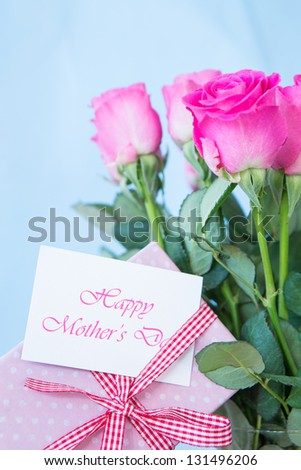 Bouquet of pink roses in vase with pink gift and mothers day message on blue background - stock photo