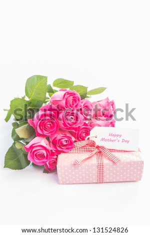 Bouquet of pink roses next to a gift with a  happy mothers day card on a white table - stock photo