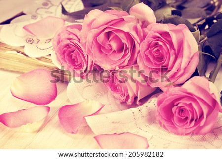 bouquet of pink roses, old book on a wooden background in vintage style