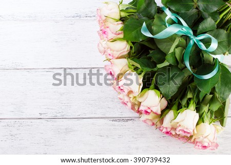 Bouquet of pink roses with blue ribbon for present on a vintage wooden background, copy space, top view - stock photo
