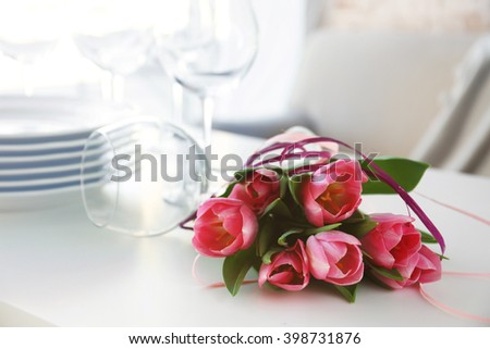 Bouquet of pink tulips and plates on wooden table. - stock photo