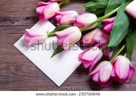 bouquet of pink tulips and postcard on wood - stock photo