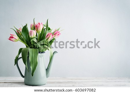 Bouquet of pink tulips in vase over  blue background