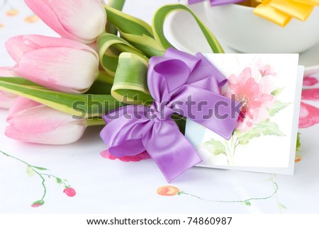 bouquet of pink tulips with purple bow and greeting card - stock photo