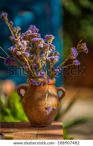 Bouquet of purple dry flowers in an old rustic vase - stock photo