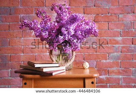 Bouquet of purple lilac flowers on red brick wall background - stock photo