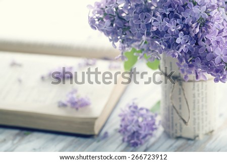 Bouquet of purple lilac spring flowers with an open book and vintage hazy editing - stock photo