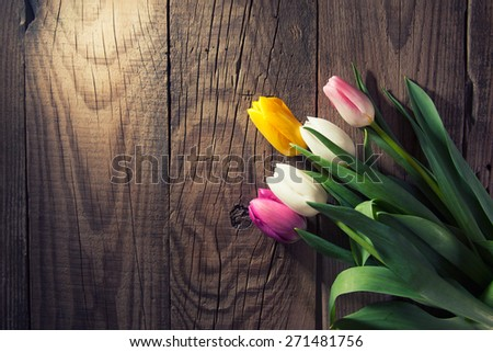 bouquet of purple, yellow and white tulips on a wooden background - stock photo