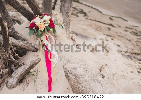 bouquet of red and white roses with eucalyptus and ribbons lie on the tree branch in sand