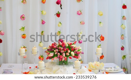 Bouquet of red and yellow tulips on a festive table. Wedding decoration. - stock photo