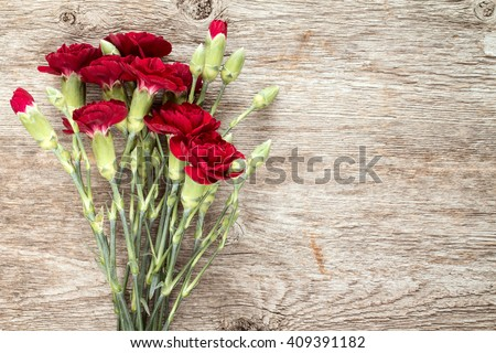 Bouquet of red carnations on the wooden background with copy-space - stock photo