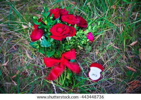 bouquet of red roses and a ring in the grass