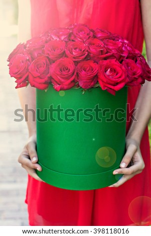 Bouquet of red roses in a box  in the hands of the girl. - stock photo