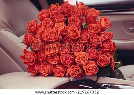 Bouquet of red roses in luxury car. Composition for a romance or anniversary. - stock photo